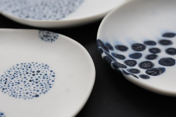 """""""Over the past fifteen years, I've moved between found objects, wood and ceramic as preferred sculpture media. I consider myself a sculptor more than a ceramist.""""<br><br>Discs, blue wash on unglazed white porcelain, available at March in San Francisco."""