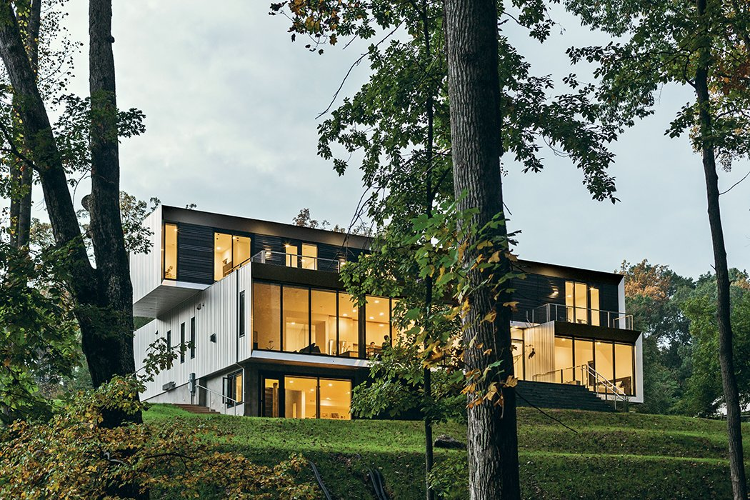 Located on a sloped wooded site, the 7,500-square-foot Bridge House encompasses two stories and a finished basement. The multigenerational abode by Höweler + Yoon Architecture embraces its sylvan setting through floor-to-ceiling glass walls and generously sized terraces on the first and second stories. Tagged: Exterior and House.  Photo 1 of 11 in This Woodland Home in Virginia Was Built for Modern, Multigenerational Living