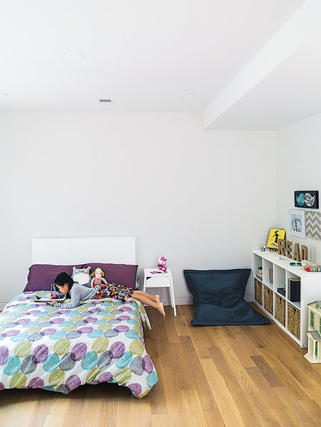 The kids' bedrooms are located on the second story. Karis's room is furnished with a Fatboy beanbag chair. Tagged: Bedroom, Bed, Shelves, Night Stands, and Storage.  Photo 7 of 11 in This Woodland Home in Virginia Was Built for Modern, Multigenerational Living