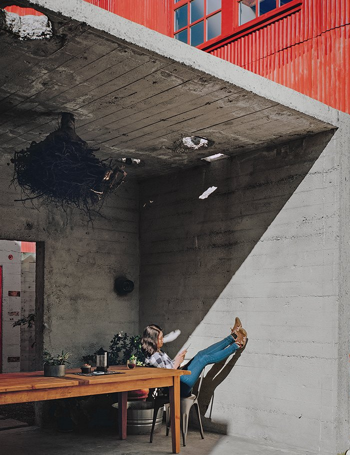 Kiyoko Loh relaxes inside a concrete structure, one of three original buildings that occupied the San Francisco property she and her husband, Elliot Loh, purchased in 2012. Working with architect Todd Davis, the couple decided to cut the bunker-like edifice in half and use it as an outdoor dining area that opens to a courtyard. Tagged: Dining Room, Table, Pendant Lighting, and Chair.  Photo 1 of 11 in Abandoned Industrial Compound Becomes a Modern Home Base