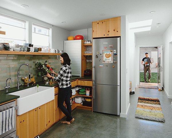The kitchen features custom casework by Peter Doolittle, dark-green slate countertops from Hamilton-Schwarzhoff, and a Heath Ceramics backsplash.