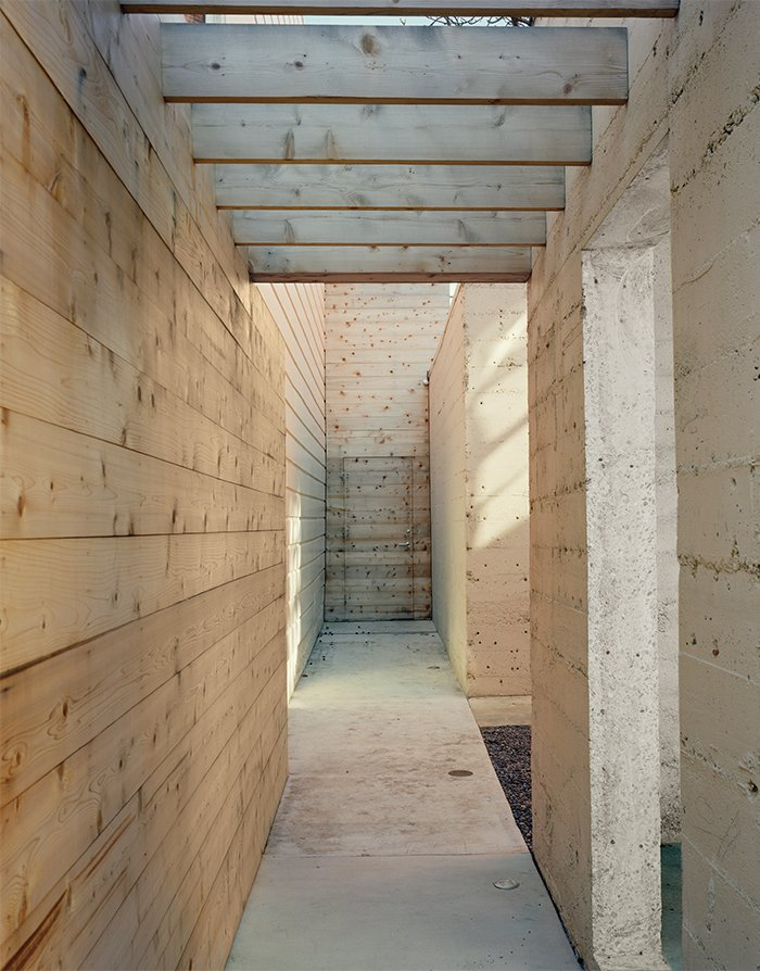 Once inside the property, a cedar-clad walkway runs parallel to the open concrete pavilion. Tagged: Hallway and Concrete Floor.  Photo 9 of 11 in Abandoned Industrial Compound Becomes a Modern Home Base
