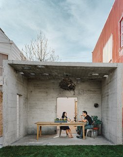 """Abandoned Industrial Compound Becomes a Modern Home Base - Photo 10 of 11 - The couple uses the pavilion for outdoor dining. From there, the property opens to a small courtyard, and finally culminates at the main house, which holds one bedroom, a kitchen, a living-dining space, and a """"flex"""" room."""