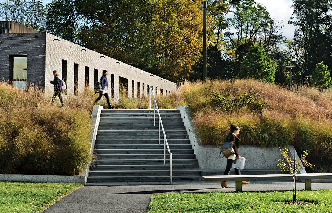 Making use of a sculpted berm, Tod Williams Billie Tsien Architects built identical 21,500-square-foot dormitory buildings at Haverford College without interior stairwells or elevators, freeing up room for courtyards and more generously sized common spaces. Tagged: Exterior, Brick Siding Material, Stone Siding Material, and Concrete Siding Material.  Photo 9 of 11 in 11 Innovative and Modern Schools Where Creativity and Good Design Rule from Cutting-Edge Dorms Embrace The Landscape with No Need for Elevators or Interior Stairs