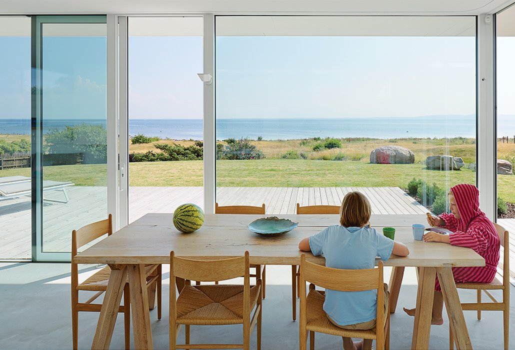 Oskar and Karl, 12 and 9, share breakfast at their family's summer getaway in Sweden. The table is from ILVA, and the CH36 chairs by Hans Wegner are from Carl Hansen & Søn. Tagged: Dining Room and Table.  Photo 8 of 20 in Pull Up a Chair in One of These 20 Modern Dining Rooms from A Scandinavian Summer Home Built for Surf, Sports, and Sun