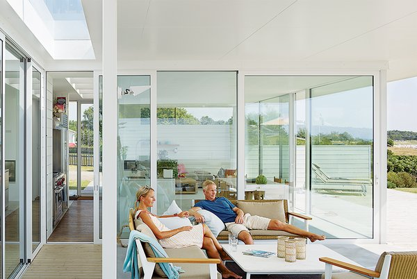 """Henrik and Karin Lepasoon relax in their outdoor seating area that faces the ocean. They purchased the property in 2005 and began building five years later. """"We used to take road trips in Europe every summer,"""" says Henrik, """"but when Oskar was born we thought it would be nice to be in one place."""""""