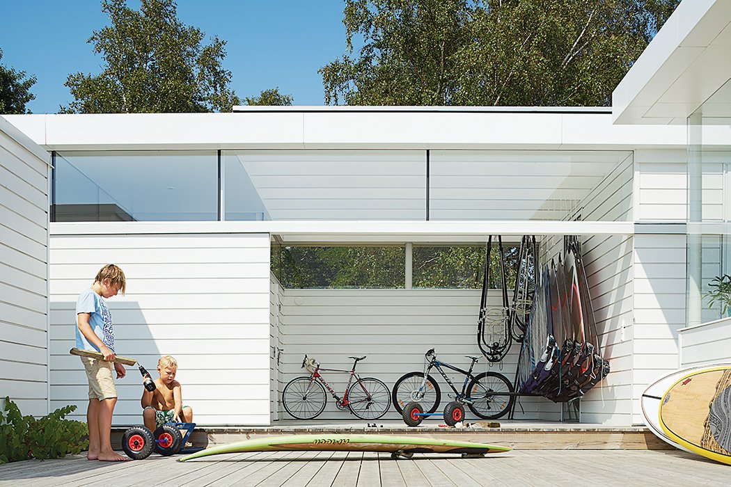 "The family are avid fans of watersports of all stripes: ""Windsurfing and the stand-up paddling board—the beach is right outside,"" says Henrik. ""It's a fun house."" Tagged: Outdoor, Large Patio, Porch, Deck, and Wood Patio, Porch, Deck. A Scandinavian Summer Home Built for Surf, Sports, and Sun - Photo 3 of 10"