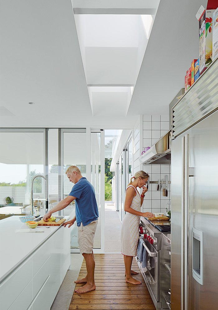 In the kitchen, the couple prepare a meal. The Multiform island is topped in Corian; the oven and hood is from Wolf. Tagged: Kitchen, Light Hardwood Floor, and Refrigerator.  Photo 4 of 10 in A Scandinavian Summer Home Built for Surf, Sports, and Sun