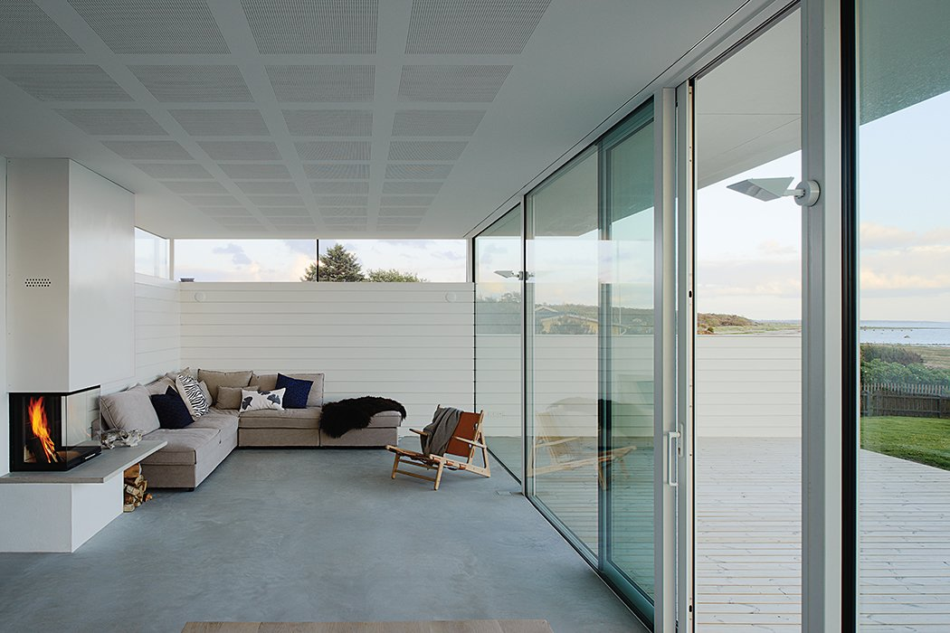The living room features a sofa by Sits and a 1950 Hunting Chair by Børge Mogensen. Tagged: Living Room, Concrete Floor, Chair, Sofa, Wood Burning Fireplace, and Standard Layout Fireplace. A Scandinavian Summer Home Built for Surf, Sports, and Sun - Photo 6 of 10