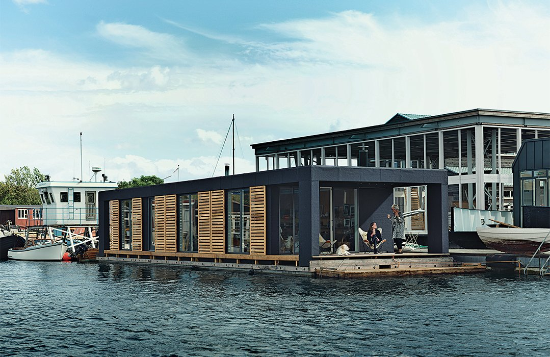 Lisbeth Juul and Laust Nørgaard drew upon their years of experience living on the water to design and build an 860-square-foot floating home in Copenhagen Harbour. The home's minimal form and furnishings reflect the residents' desire to downsize following three years on land. Tagged: Exterior, Flat RoofLine, Wood Siding Material, Glass Siding Material, and Boathouse Building Type.  Photo 1 of 9 in Each Day at This Floating Home Begins With a Swim, Just Two Feet From Bed