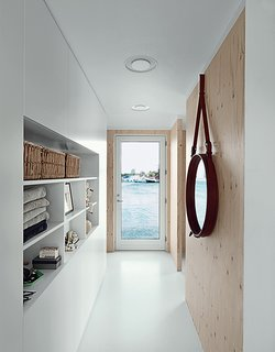 The narrow entrance hall faces another door, which opens seaward. Built-in cabinets serve as both storage and display. The porthole mirror is by Jacques Adnet.