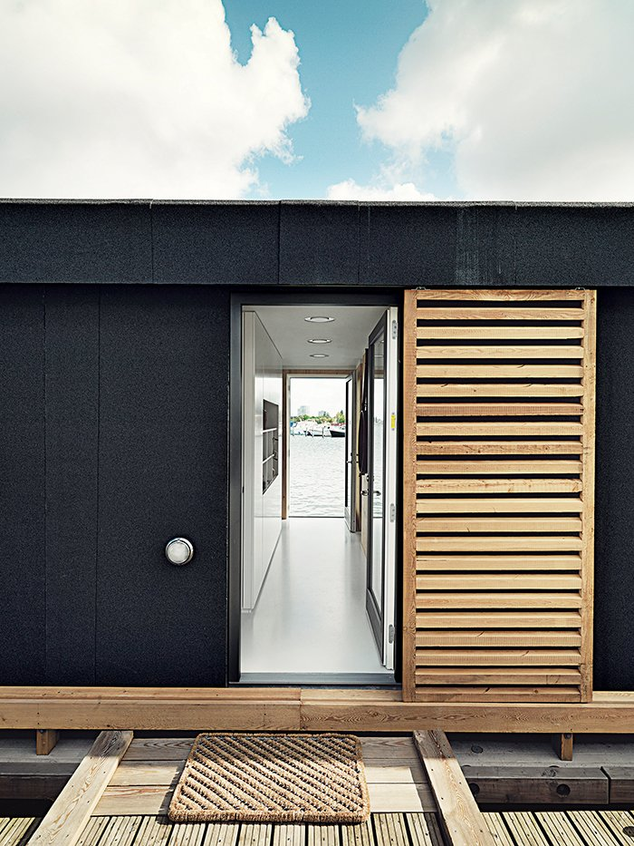 Outside, larch-wood shutters offer the residents privacy. Tagged: Doors, Sliding Door Type, Wood, and Exterior.  Photo 3 of 9 in Each Day at This Floating Home Begins With a Swim, Just Two Feet From Bed
