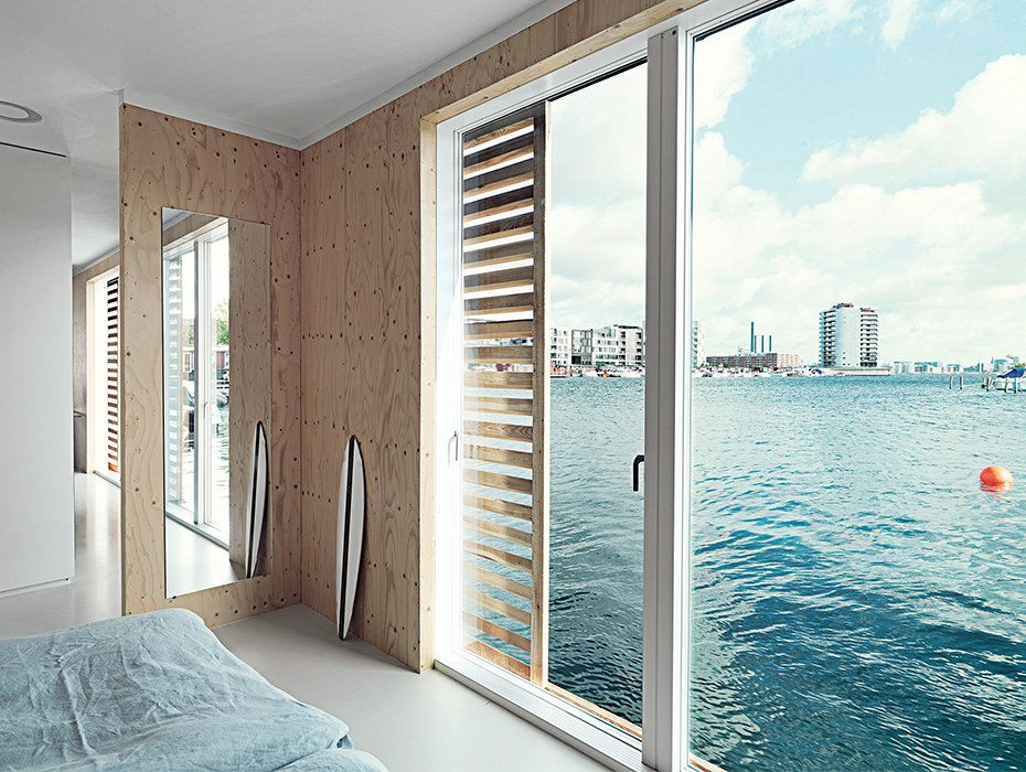 Glass doors grant the bedroom an immediate connection to the water. Each Day at This Floating Home Begins With a Swim, Just Two Feet From Bed - Photo 6 of 9