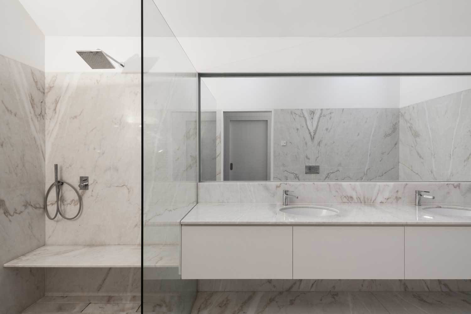 The bathrooms are lined in luxurious Estremoz marble. Tagged: Bath Room, Marble Counter, Undermount Sink, Marble Floor, and Enclosed Shower. House of Four Houses by Laura C. Mallonee