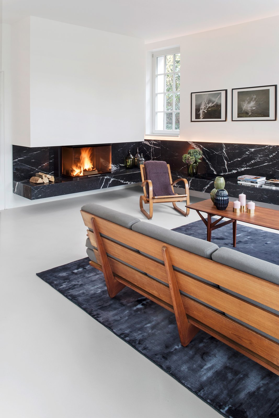 Nero Marquina marble is used in multiple rooms. In the living room, a strip of stone defines a bench that wraps around the space. Both the sofa and armchair are vintage. Ways to Define Spaces With Area Rugs by Heather Corcoran