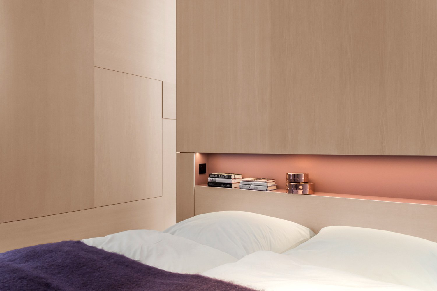 An elegant built-in shelf lies above the bed. Bedrooms by Dwell