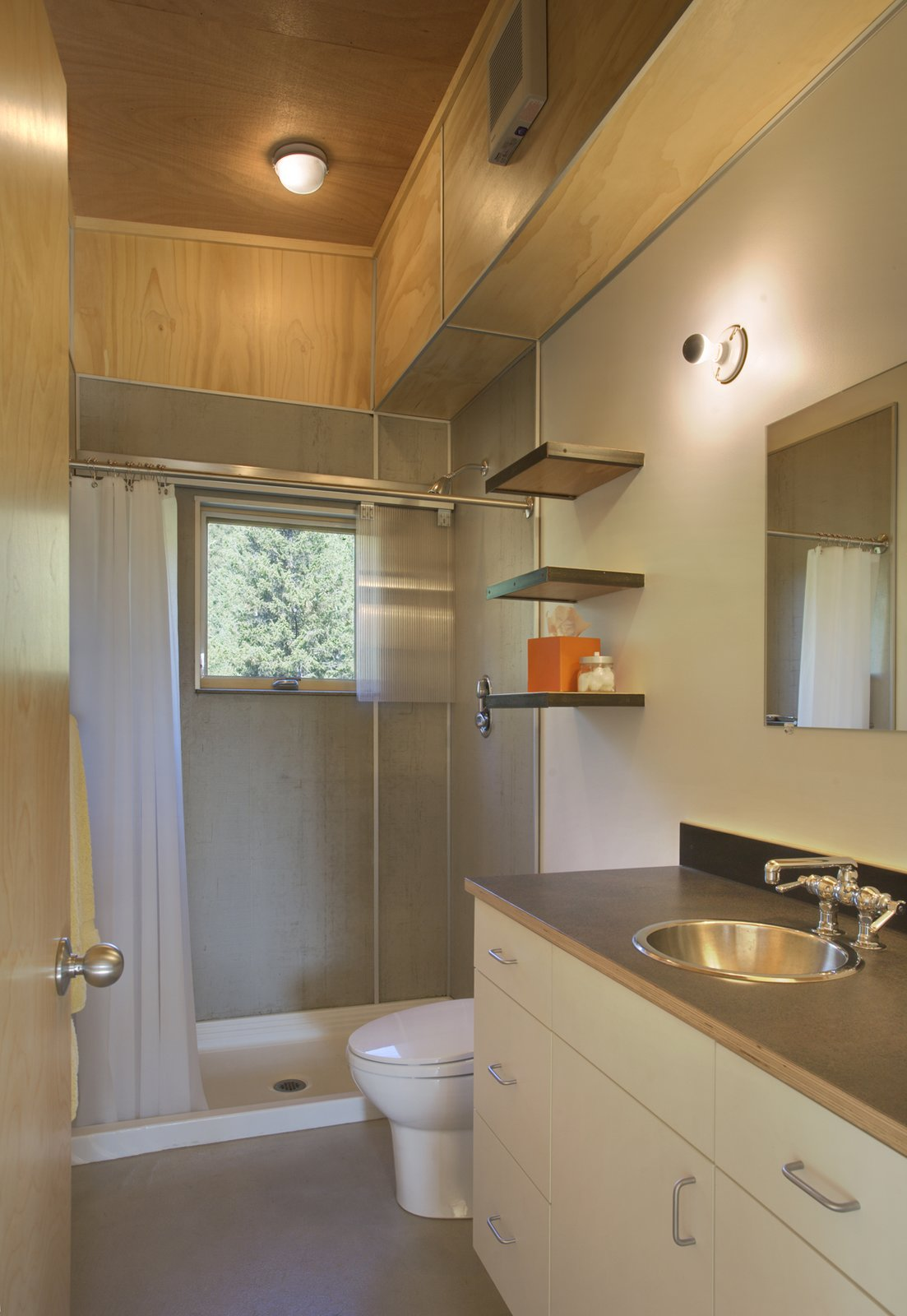 The entrance is immediately flanked on its left by a mudroom for hiking gear and the bathroom.  Bathroom from Simple Cabin Embraces Its Mountain Setting