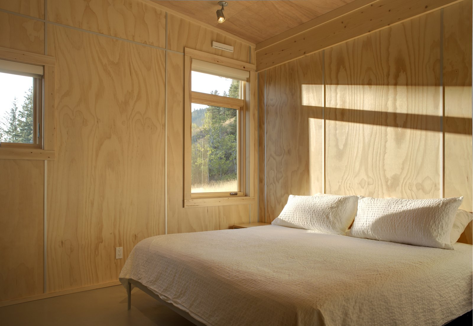 The bedroom is to the immediate right of the entrance; the architects selected plywood for interior surfacing for the warm tones it provided. The aluminum spacers allow for easy installation—they have greater tolerances for gaps as compared to other joints—while doubling as a decorative element.  Bedroom by Lauren Gundlach from Simple Cabin Embraces Its Mountain Setting