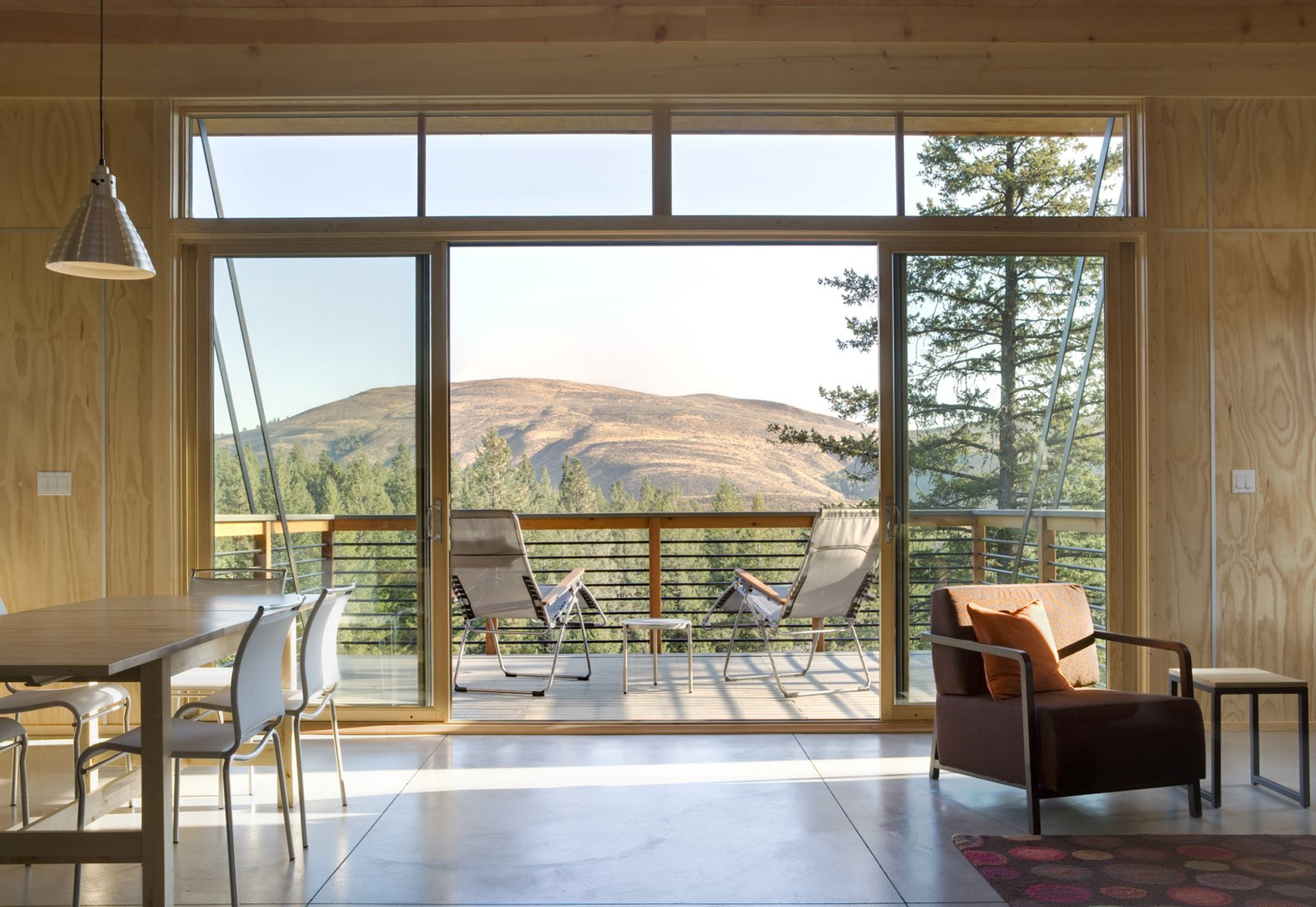 Supported by steel strips, the balcony extends outwards to meet the valley below. Fully-glazed sliding doors and a clerestory window provide a view.