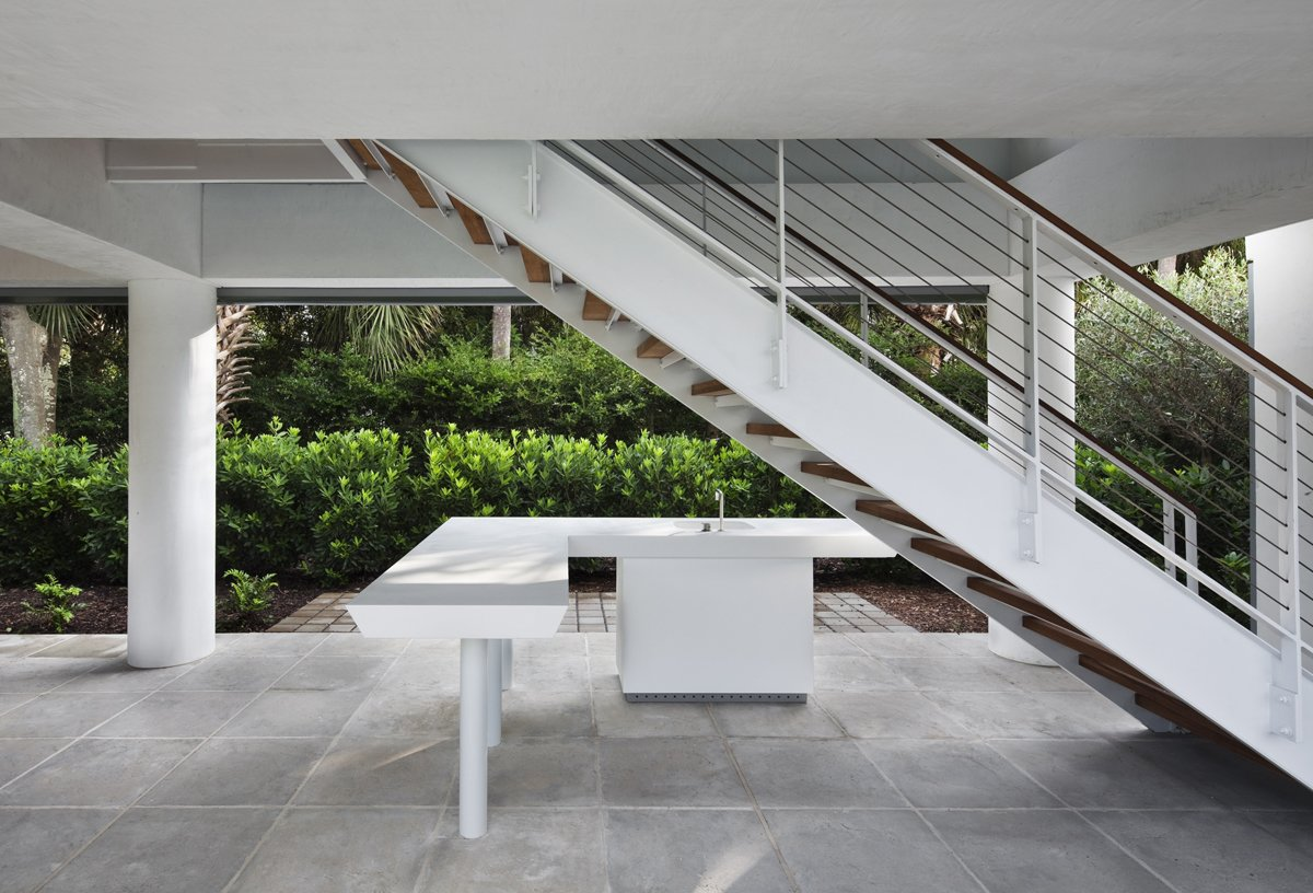 Underneath the raised pavilion, the architect carved out an updated version of the classic Southern veranda. This one sports a minimalist outdoor kitchen and all-white accents with a cypress ceiling.  Photo 3 of 6 in Summer-Ready Modern Pavilion in South Carolina