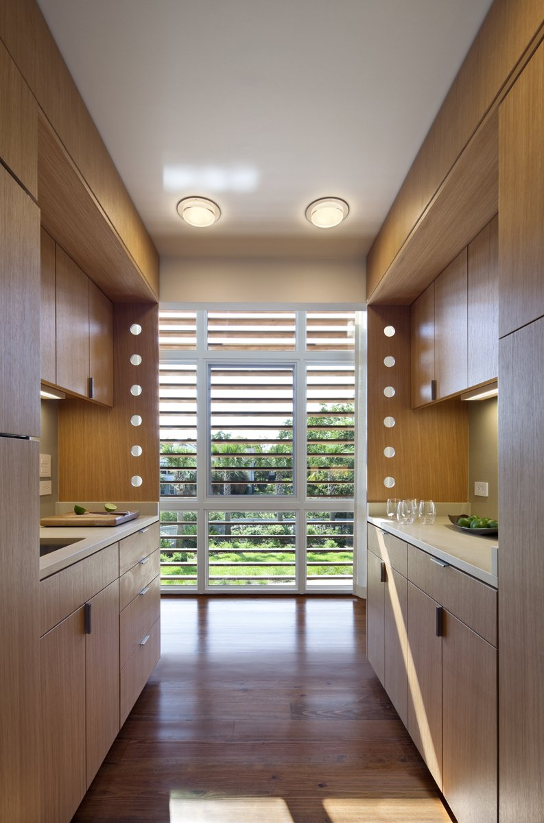 A sleek galley kitchen packs function and style into a small space. Tagged: Kitchen, Wood Counter, and Light Hardwood Floor.  Photo 5 of 6 in Summer-Ready Modern Pavilion in South Carolina