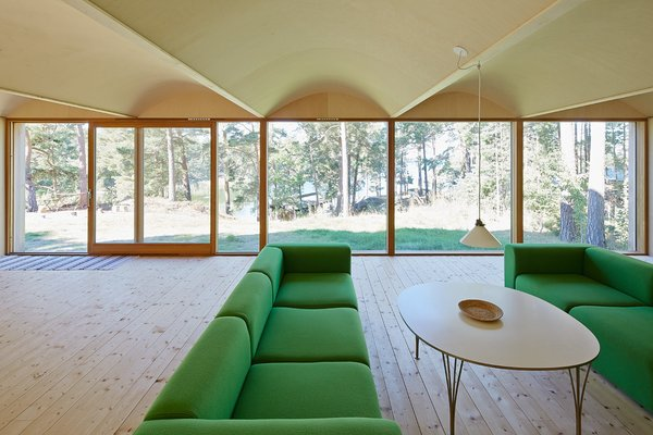 The site faces the sea but is surrounded by tall pines. The green sofas are from Hay.