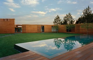 "Modern Wood-Lined Family Home in the Hamptons - Photo 1 of 9 - As the facade of a Bates Masi-designed home in Water Mill, New York, rises from eight to 14 feet high, the mahogany planks subtly widen. ""It was quite a demand to make of the contractor,"" architect Paul Masi says. ""But the design was so much about traveling through the site and weaving [the house] together with the deck."""