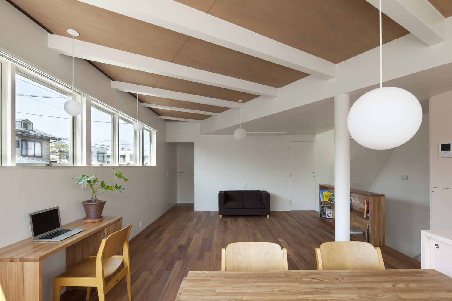 The ceilings of the two houses were at slightly different heights, an incongruity Nakasi played up for visual punch. He exposed the beams in the higher ceiling and painted them white to match the smooth finish of the lower one. The desk beneath the window is from Muji.
