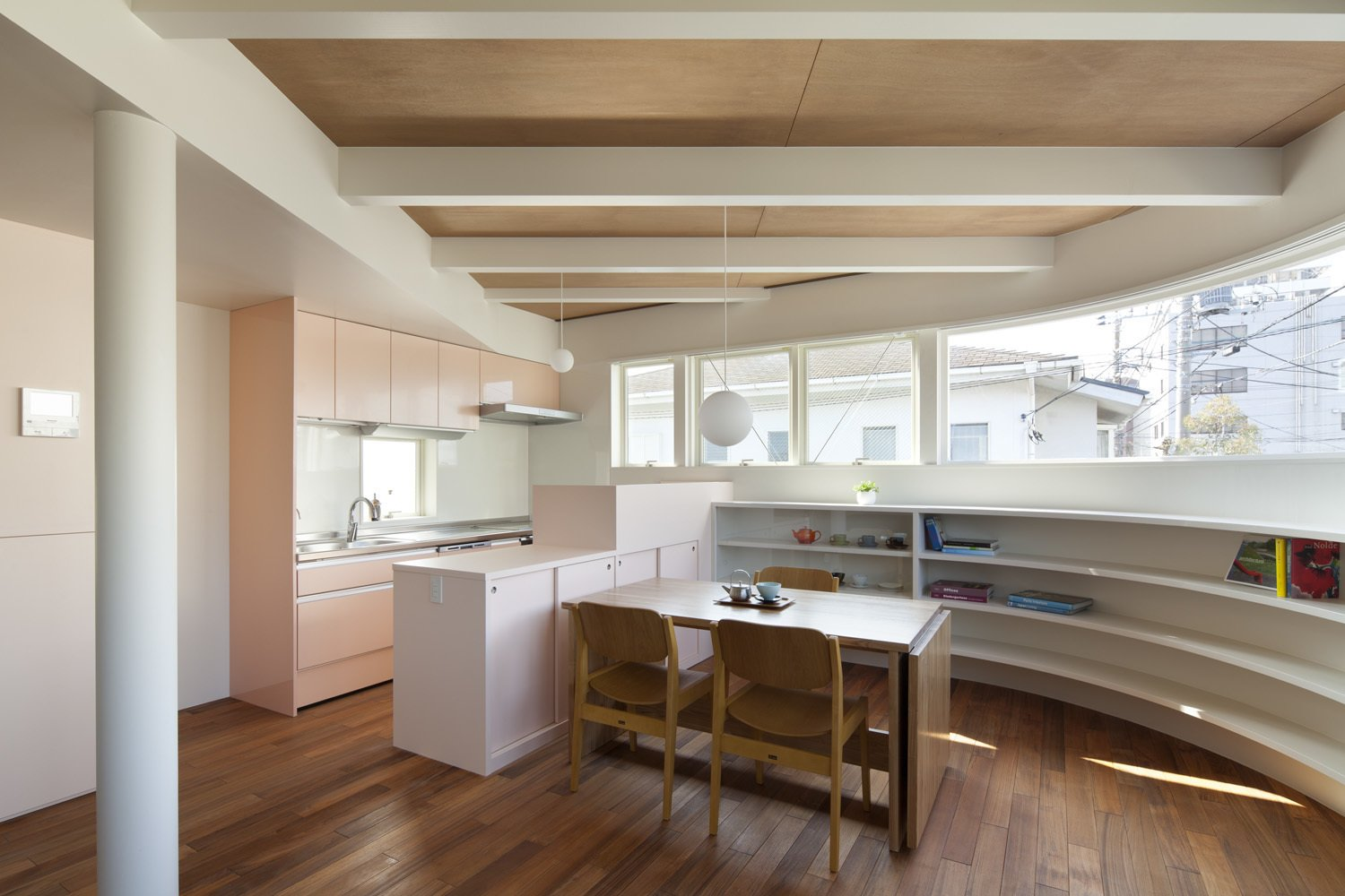 The kitchen and dining area features an integrated system by LIXEL, a custom-made table, and Tendo chairs. A bespoke, curved bookshelf wraps around the wall beneath a panoramic window.
