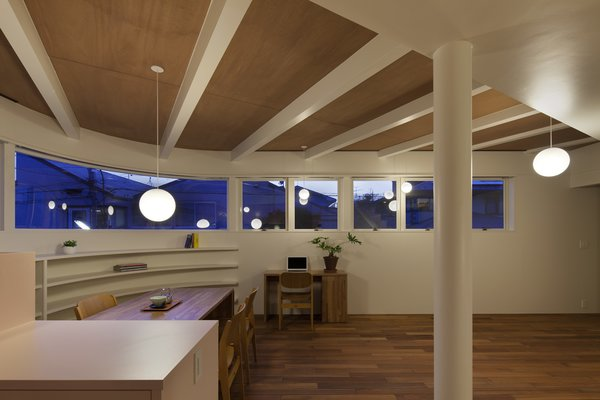 Globe pendant lights by Panasonic hang whimsically throughout the house. The strip window sits high for privacy. Photo 7 of Half & Half House modern home