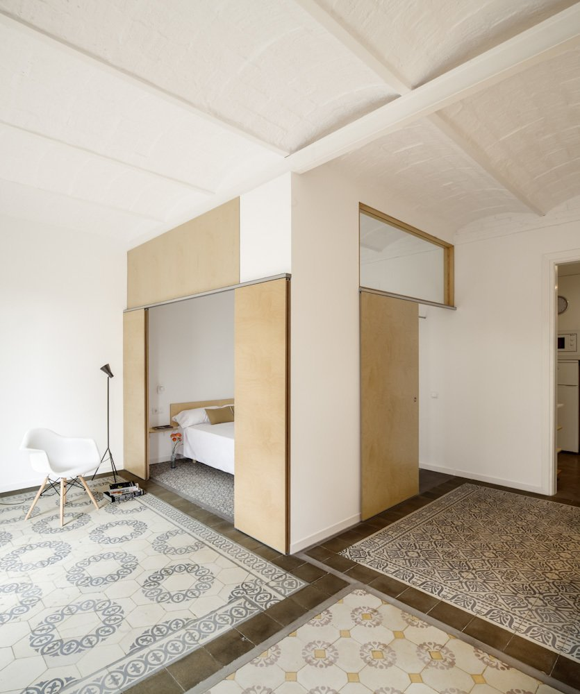 This renovated apartment in Barcelona plays with subtle color contrasts, such as the chromatic tile mosaics and the blond wood used for sliding doors and benches.  Photo 4 of 13 in 12 Creative Ways to Use Tile in Your Home from 1930s Barcelona Apartment Gets a Minimal Makeover