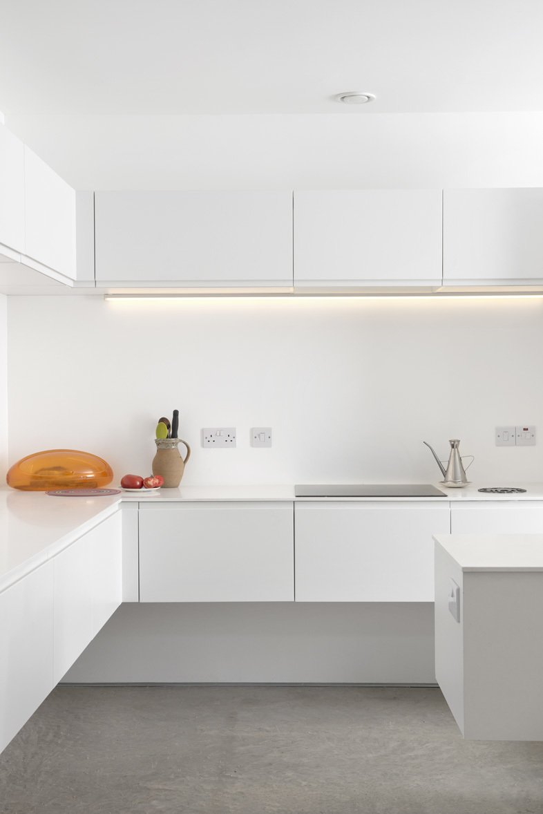 The stark white minimalist kitchen features quartz countertops, a Gessi Oxygene tap, a 1810 Company Zenuno sink, and energy-efficient Bosch appliances.