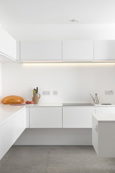 The stark white minimalist kitchen features quartz countertops, a Gessi Oxygene tap, a 1810 Company Zenuno sink, and energy-efficient Bosch appliances. Photo 6 of Ferrum House modern home