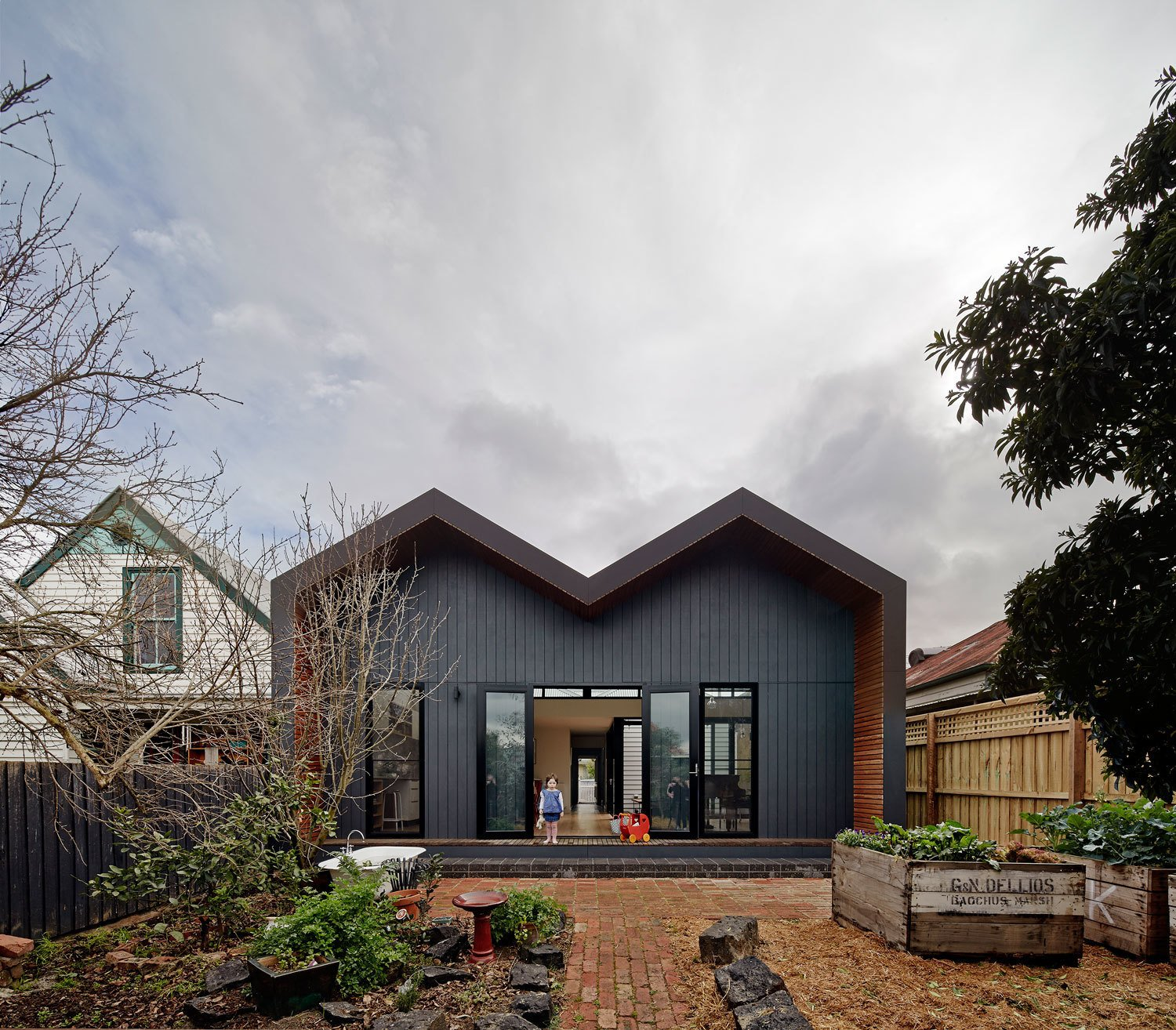 The extension sits on the property's north side. Its zig-zag shape is a continuation (and reinterpretation) of the more traditional double hip roof of the existing house. The new construction combines Shadowclad boards, a Lysaght Longline steel roof, and Blackbutt eucalyptus decking.  M House by Laura C. Mallonee