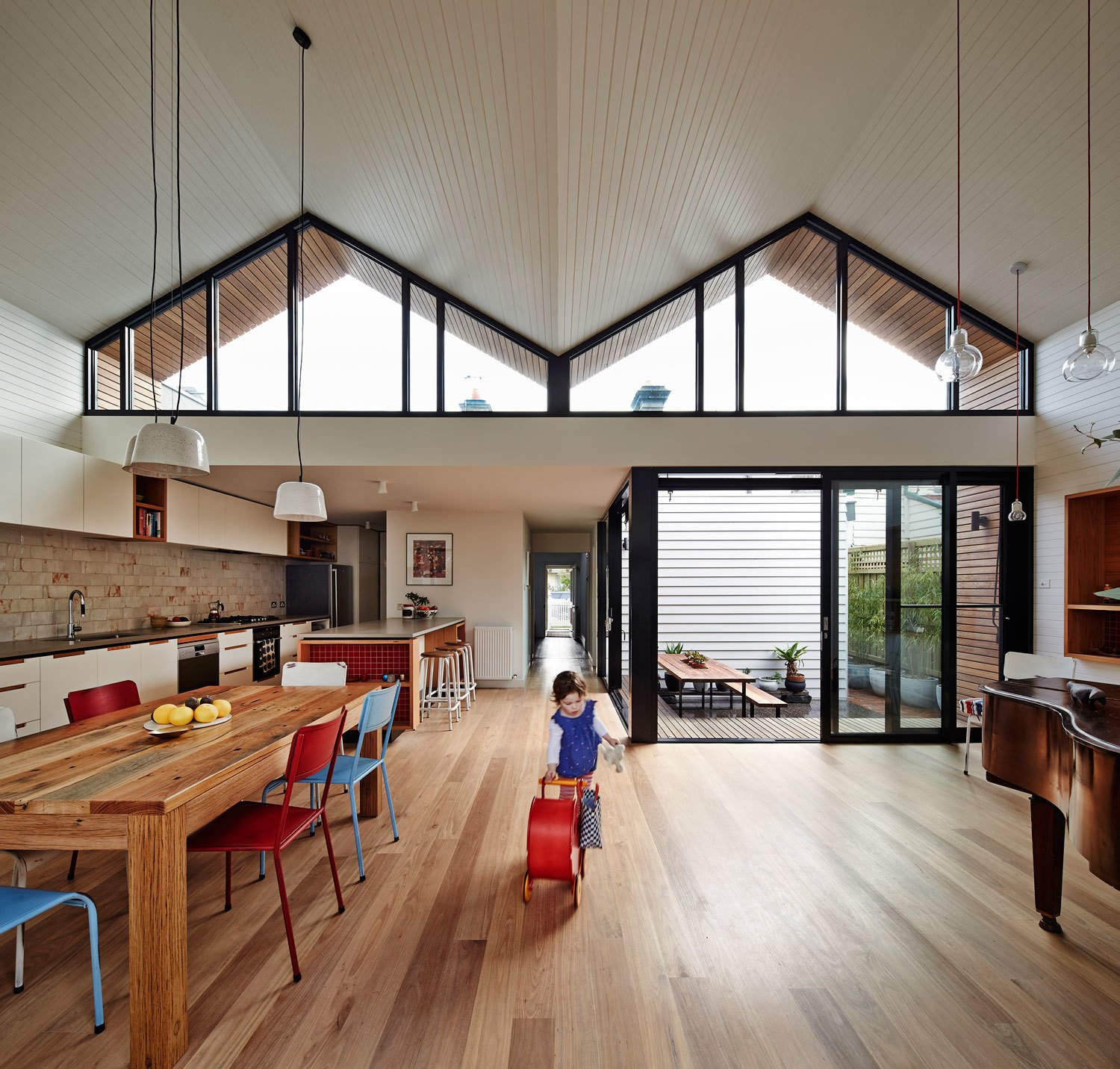 "The roof's geometric shape helps the interior feel more expansive than it is. Messmate timber floorboards and painted ceiling boards follow the lines of its double hip and draw the eyes upward. Powder-coated black aluminum window frames also accentuate its form. ""We like the contrast of the white space with the gutsy black frames,"" Bright says."