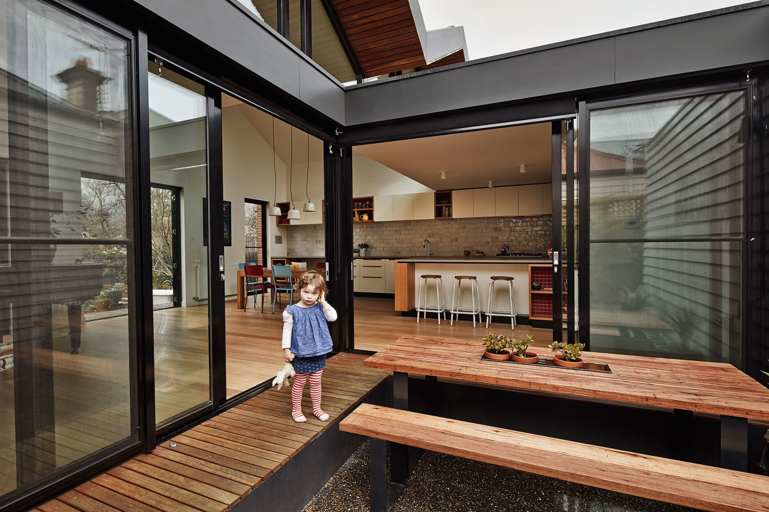 The architects pulled away the roof at the house's center to create a courtyard where the residents can enjoy meals. The ground sits below floor level, which means that the wraparound eucalyptus deck can also serve as a bench. Tagged: Outdoor, Wood Patio, Porch, Deck, and Small Patio, Porch, Deck. M House by Laura C. Mallonee
