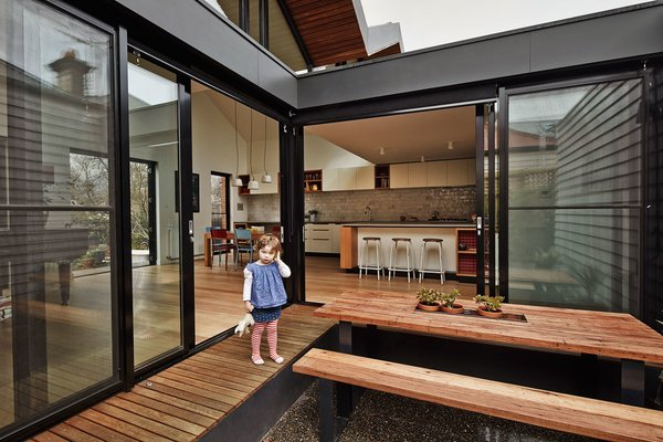 The architects pulled away the roof at the house's center to create a courtyard where the residents can enjoy meals. The ground sits below floor level, which means that the wraparound eucalyptus deck can also serve as a bench. Photo 4 of M House modern home
