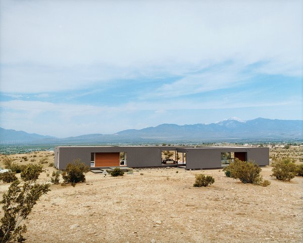 Deep porches and limited openings shelter the West side of this modular home from the harsh elements of the California desert.