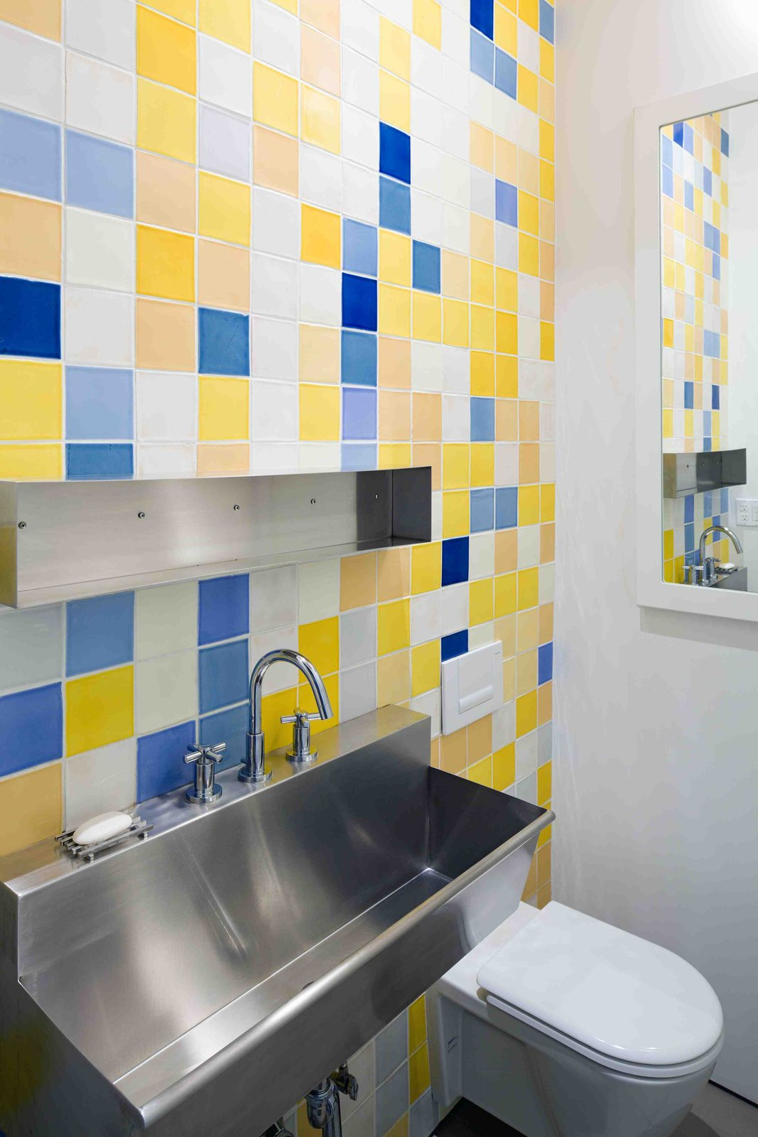 The bathroom tiles were a point of contention: Bartlett wanted Mexican tiles, while Berridge's design favored a bare-bones, Donald Judd-like approach in keeping with the warehouse experience.  The compromise was that he used industrial sinks and designed the stainless-steel hardware to be as utilitarian as possible, and commissioned a set of plain tiles with a strict color palette of five yellows, five blues and five whites, derived from Bartlett's work. She then arranged them on one wall as she would one of her installations. That way, both upstairs and downstairs bathrooms have Jennifer Bartlett originals on the wall.