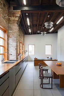 20 Best Modern Kitchen Counters - Photo 9 of 20 - What the original building lacked in period detailing, it made up for with massive interior spaces, natural light, and a hardy palette of wood and raw brick. Working with these loft signatures, David developed the gigantic kitchen on the upper floor running the width of the building, with a 37-foot-long solid walnut counter on top of stainless-steel cabinets. This unites the dining, cooking, and social spaces that run the length of the front facade on the upper floor.