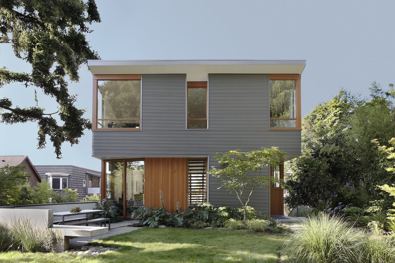 """""""Durability drove the selection of metal panels,"""" Schaer says of the home's industrial exterior. Manufactured by AEP SPAN from corrugated cladding, it looks like zinc but costs significantly less. It also contrasts nicely with the natural siding and trim. """"All of the wood inside and out is Douglas Fir, the predominant wood species in the northwest,"""" Schaer explains. Tagged: Exterior and House.  Photo 1 of 11 in Seattle Home Carefully Blocks Out Neighbors, While Celebrating Natural Surroundings"""