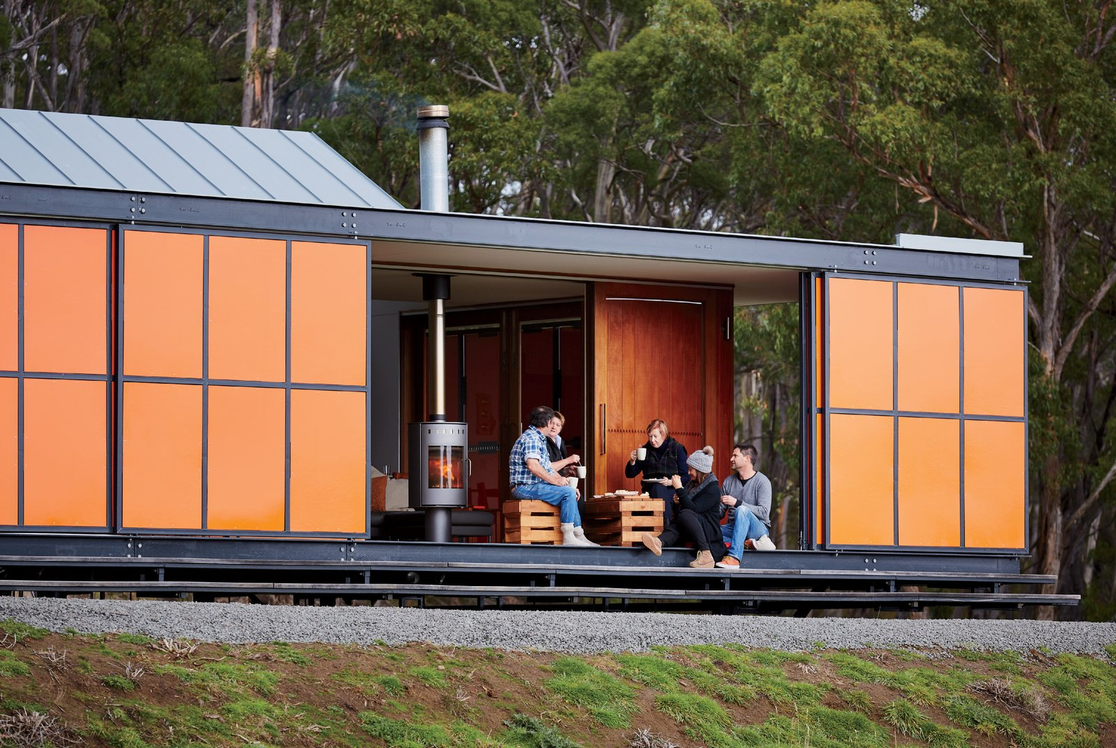 """The home was designed as a """"box within a box,"""" in which two interior structures—an open-plan living space and two en suite bedrooms—sit within its exterior envelope. Inspired by the region's fiery orange lichen and the indigenous waratah shrub's bright flowers, the colorful exterior panels are made of heavy-duty galvanized steel to guard from Tasmanian winds, which can reach up to 60 miles per hour."""