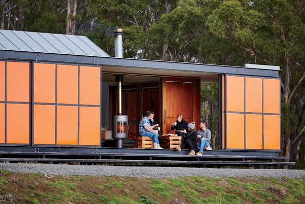 """The home was designed as a """"box within a box,"""" in which two interior structures—an open-plan living space and two en suite bedrooms—sit within its exterior envelope. Inspired by the region's fiery orange lichen and the indigenous waratah shrub's bright flowers, the colorful exterior panels are made of heavy-duty galvanized steel to guard from Tasmanian winds, which can reach up to 60 miles per hour.  Photo 2 of 10 in An Off-the-Grid Prefab that Combines Open Plan Living with Rugged Durability"""