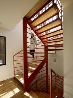 "Fabricated by Stocklin Iron Works and designed by Nebolon, the orange staircase features steel railings and treads made from IKEA wood butcher blocks. ""We designed the open staircase to make the trip to the second floor fun,"" the architect says."