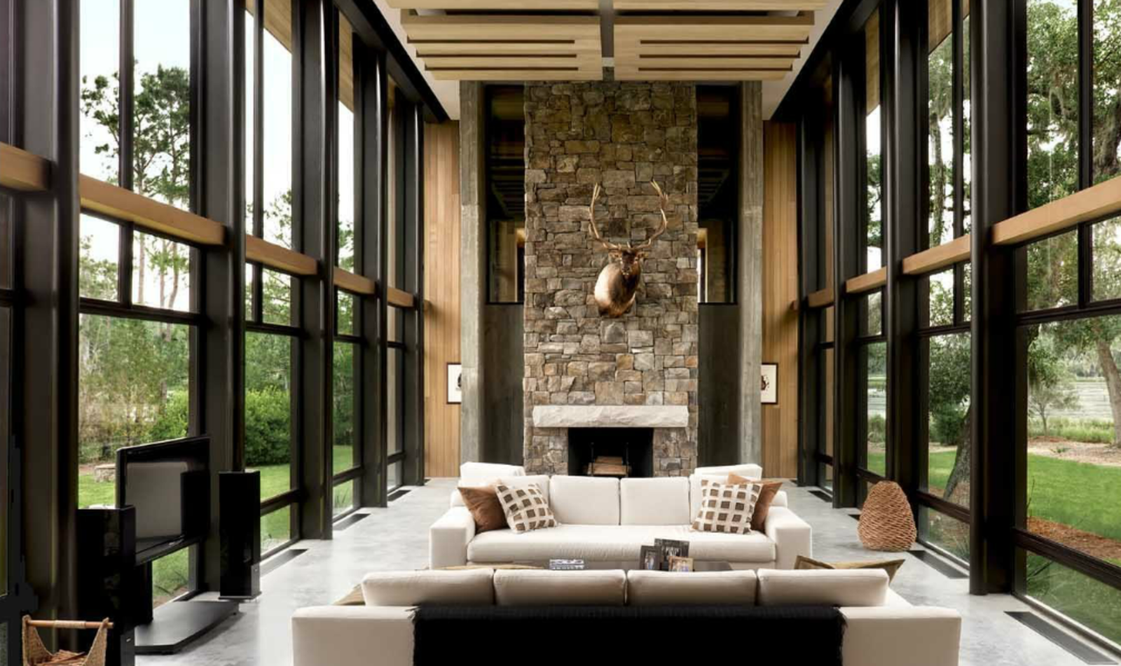 The grand, glass-walled great room is a loft-like space that incorporates living room and dining area. A bedroom and bathroom are located on a lofted mezzanine level, over the kitchen, pantry, and utility room.  97+ Modern Fireplace Ideas by Dwell from A Modern Home in a South Carolina Marsh