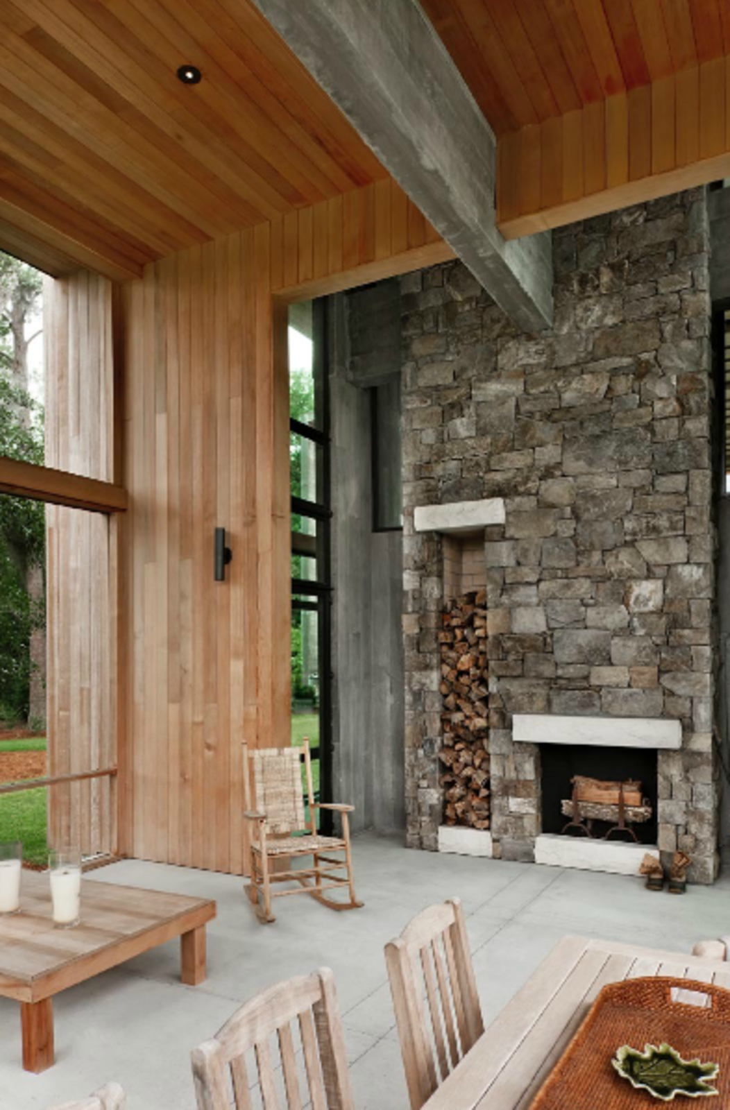 Choate selected maintenance-free materials for the project wherever possible, including the stone on this fireplace, which includes built-in storage for firewood. The stone extends 25 feet up to the wood-clad ceiling, emphasizing the home's grand scale.  97+ Modern Fireplace Ideas by Dwell from A Modern Home in a South Carolina Marsh