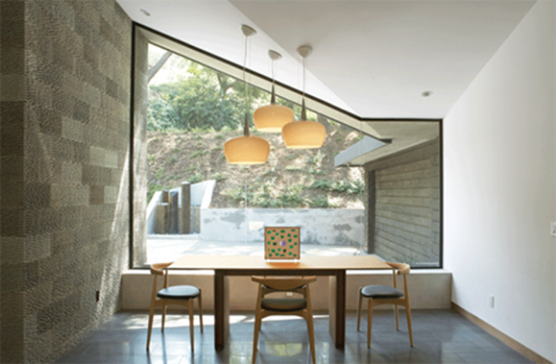 The dining area of the Kim Residence is encased in glass walls and doors, lending a sense of dining al fresco.