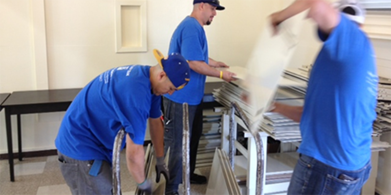 An installation crew from ANEW nationwide network assembling donated workstations at Samuel Gompers Middle School in Watts. The surplus came from partner DIRECTV.