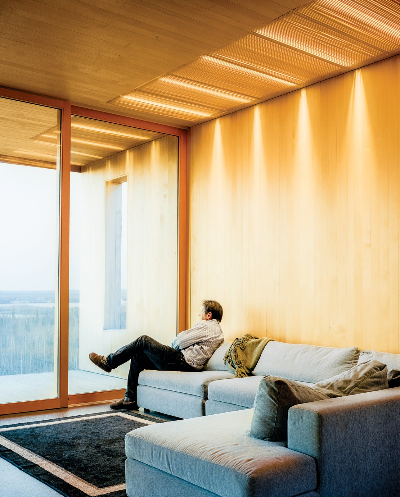 The living room features a sofa by Dellarobbia. Tagged: Living Room and Sofa. This Modern Cabin Is the Ideal HQ For a Family in Alaska - Photo 6 of 20