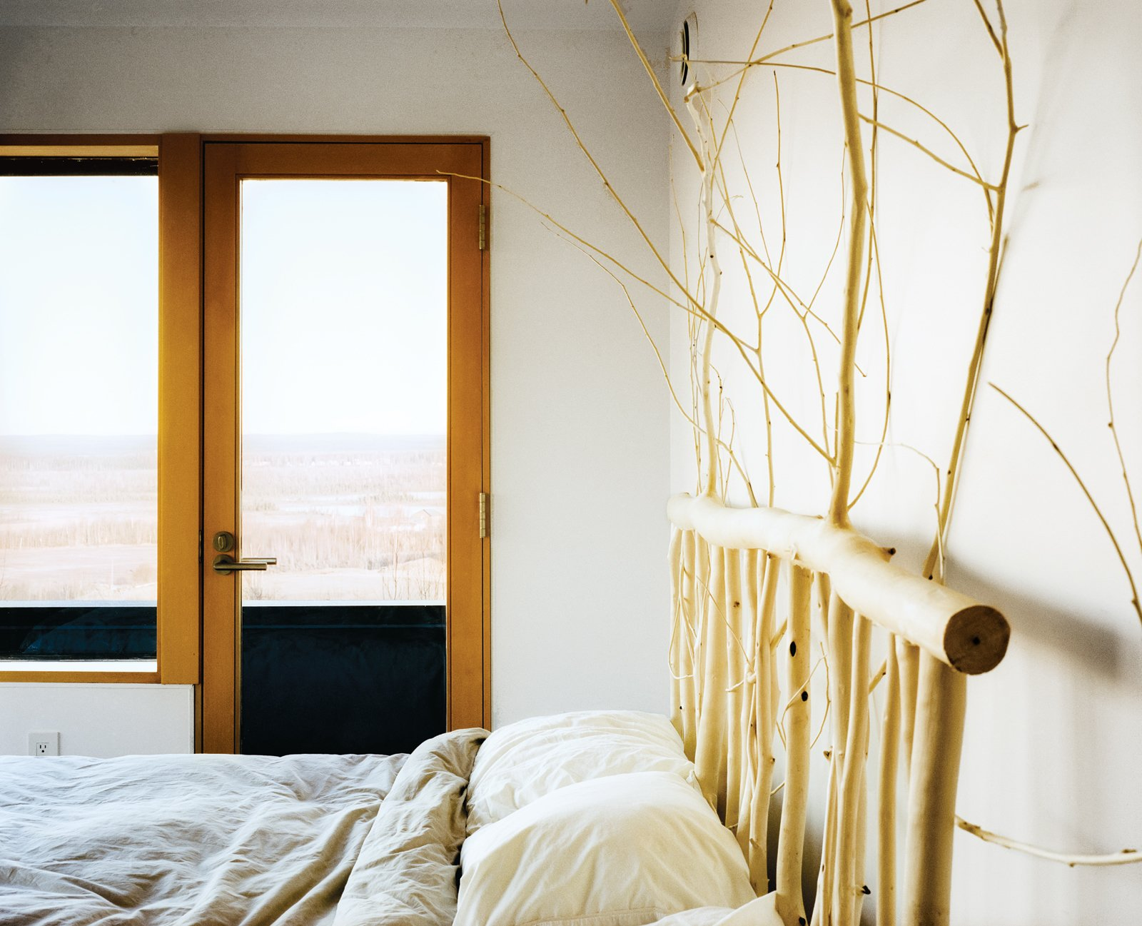 Buser designed and made the headboard in the master bedroom from local aspens. Tagged: Bedroom and Bed.  Photo 10 of 20 in This Modern Cabin Is the Ideal HQ For a Family in Alaska
